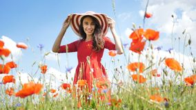 Happy young woman in red dress and big hat Enjoying Nature. Beauty Girl Outdoor walks on a poppy field. Freedom concept. Beauty Girl over Sky and Sun stock video