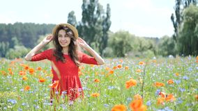 Happy young woman in red dress and big hat Enjoying Nature. Beauty Girl Outdoor walks on a poppy field. Freedom concept. Beauty Girl over Sky and Sun stock footage
