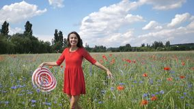 Happy young woman in red dress and big hat Enjoying Nature. Beauty Girl Outdoor walks on a poppy field. Freedom concept stock video footage
