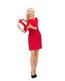 Happy young woman in red dress with gift box Stock Image