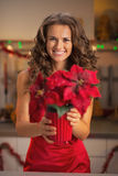 Happy young woman in red dress holding christmas rose in kitchen Royalty Free Stock Photos