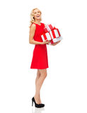 Happy young woman in red dress holding gift boxes Royalty Free Stock Image