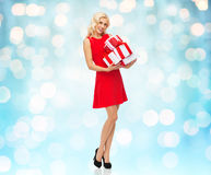 Happy young woman in red dress holding gift boxes Royalty Free Stock Photo