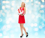 Happy young woman in red dress holding gift boxes Stock Image