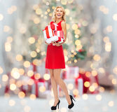 Happy young woman in red dress holding gift boxes Royalty Free Stock Photography