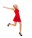 Happy young woman in red dress jumping high Stock Photography