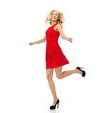 Happy young woman in red dress jumping high Stock Photo