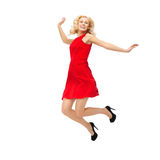 Happy young woman in red dress jumping high Stock Image