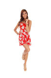 Happy young woman in red dress. A lovely happy young woman standing in front on one leg in a red dress Stock Photography