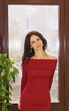 Happy young woman in red dress by the window Stock Image