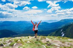 A happy young woman in red with hands up stands on top of a hill Royalty Free Stock Photos