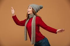 Happy young woman in red knitted sweater and gray hat posing ove. R beige background Royalty Free Stock Image