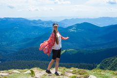 A happy young woman in red with long hair stands on top of a hill, against a backdrop of beautiful mountains Royalty Free Stock Photos