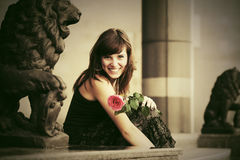 Happy young woman with a red rose on city street. Happy young fashion woman with a red rose on city street Royalty Free Stock Photos