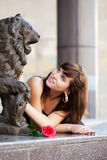 Happy young woman with a red rose. Sitting on the sidewalk Royalty Free Stock Image