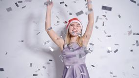 Happy young woman in Santa hat at celebration party with confetti falling stock footage