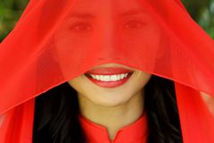 Happy Young Woman with Red Scarf Covering her Face. Close up Happy Young Asian Woman with Red Scarf Covering her Face, Looking at the Camera with a Smile Royalty Free Stock Photography