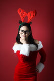 Happy young woman with reindeer attire and santa claus clothes on red background Stock Photography