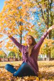 Happy young woman rejoicing in an autumn park Stock Photography