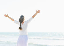 Happy young woman rejoicing at seaside . rear view Royalty Free Stock Photos