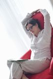 Happy young woman relax at home on sofa royalty free stock photography