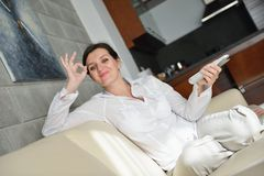 Happy young woman relax at home on sofa Royalty Free Stock Images