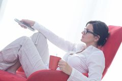 Happy young woman relax at home on sofa Stock Photos