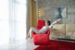 Happy young woman relax at home on sofa. In bright living room and watching tv Stock Photo
