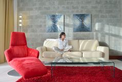 Happy young woman relax at home on sofa Stock Image