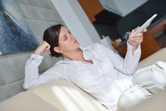 Happy young woman relax at home on sofa. In bright living room and watching tv Royalty Free Stock Photography