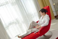 Happy young woman relax at home on sofa Royalty Free Stock Photos