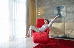 Happy young woman relax at home on sofa. In bright living room and watching tv Royalty Free Stock Image