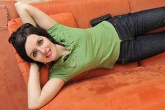 Happy young woman relax on orange sofa Royalty Free Stock Photos