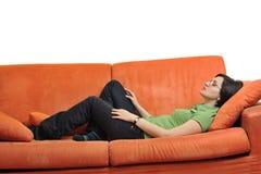Happy young woman relax on orange sofa Stock Photos