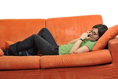 Happy young woman relax on orange sofa Royalty Free Stock Photo