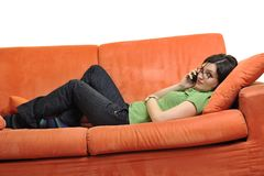 Happy young woman relax on orange sofa Royalty Free Stock Images