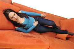 Happy young woman relax on orange sofa Stock Photography
