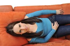 Happy young woman relax on orange sofa Stock Photo
