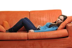 Happy young woman relax on orange sofa Royalty Free Stock Image