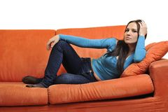 Happy young woman relax on orange sofa Royalty Free Stock Photography