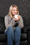 Happy young woman relaxed at home drinking coffee royalty free stock images
