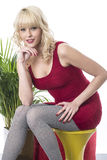 Happy Young Woman Relaxed Sitting on Stool Wearing Short Red Dress Stock Photography