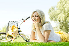 Happy young woman relaxing. Happiness young blond woman relaxing on green grass after cycling Stock Photography