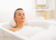 Happy young woman relaxing in bathtub. Happy young woman with brown hair relaxing in bathtub stock photo