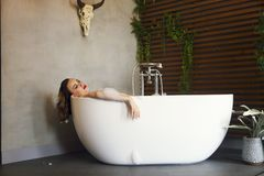 Happy young woman relaxing in bathtub. Portrait of the happy young woman relaxing in bathtub stock image