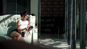 A girl is relaxing on couch and holding a book. Portrait of pretty businesswoman surfing internet on smartphone while