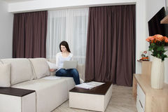 Happy young woman is relaxing on comfortable couch and using laptop at home Stock Images