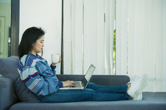 Happy young woman is relaxing on comfortable couch and using laptop at home. Photo toned Royalty Free Stock Photos