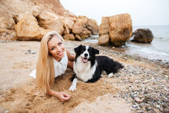 Happy young woman relaxing with her dog on the beach Royalty Free Stock Images