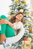 Happy young woman relaxing near christmas tree Royalty Free Stock Photos